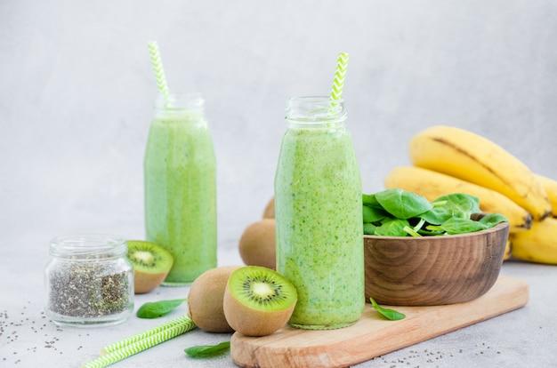 Świeże zielone koktajle ze szpinaku, banana, kiwi, jogurtu i nasion chia w szklanych słoikach ze słomką na szarej powierzchni. zdrowe odżywianie. orientacja pozioma. skopiuj miejsce