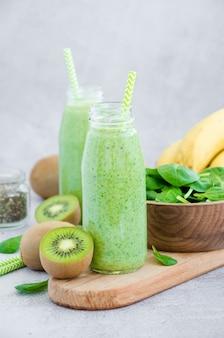 Świeże zielone koktajle ze szpinaku, banana, kiwi, jogurtu i nasion chia