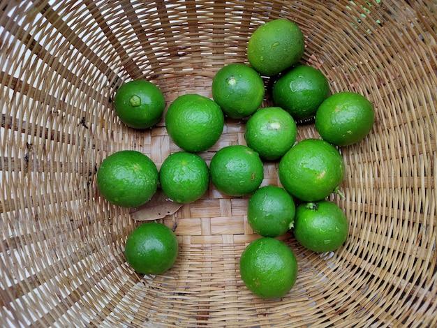 Świeże zielone limonki w małych kolorowych koszach na plecionym bambusowym talerzu. tajski tradycyjny świeży rynek.