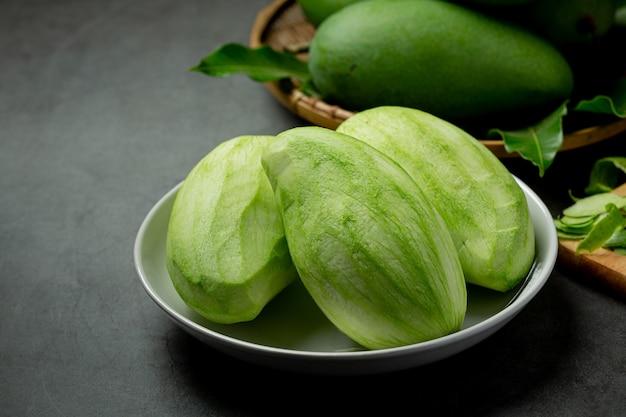 Świeże zielone mango na ciemnej powierzchni