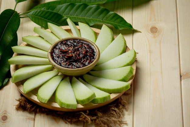 Świeże zielone mango z sosem ze słodkich ryb, zanurzone na drewnianej powierzchni