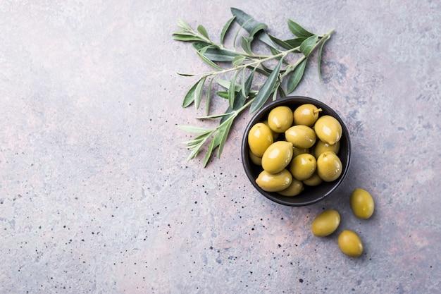 Świeże zielone oliwki w misce i gałązka oliwna na rustykalnym kamieniu