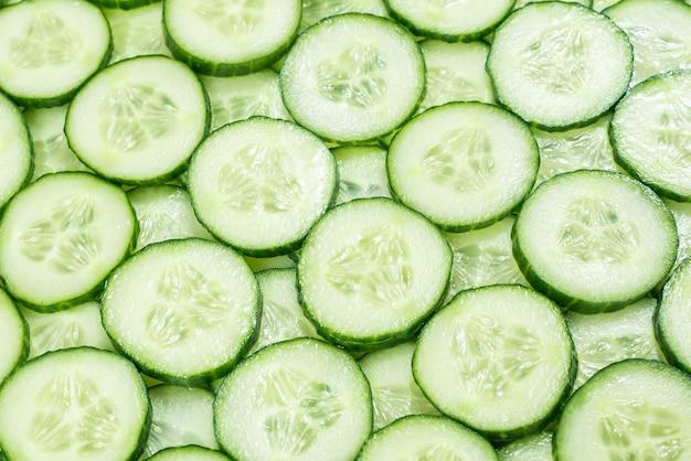 Świeże zielone plasterki ogórka jako tło. widok z góry.