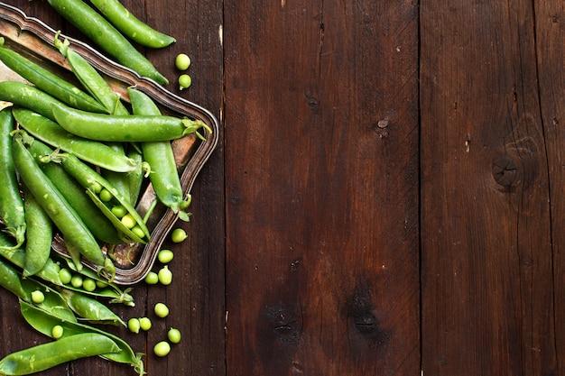 Świeże zielone strąki z rynku rolników na drewnianym stole