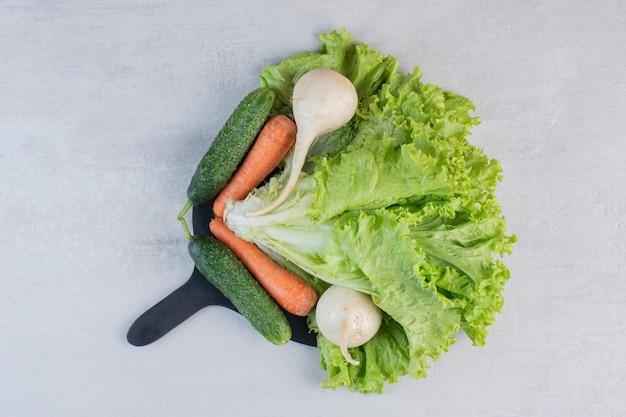 Świeże zielone warzywa i marchewki na czarnej tablicy. wysokiej jakości zdjęcie