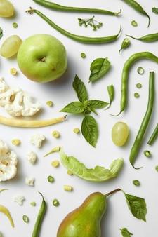 Świeże zielone warzywa i owoce na białym stole. detox, dieta lub koncepcja zdrowej żywności