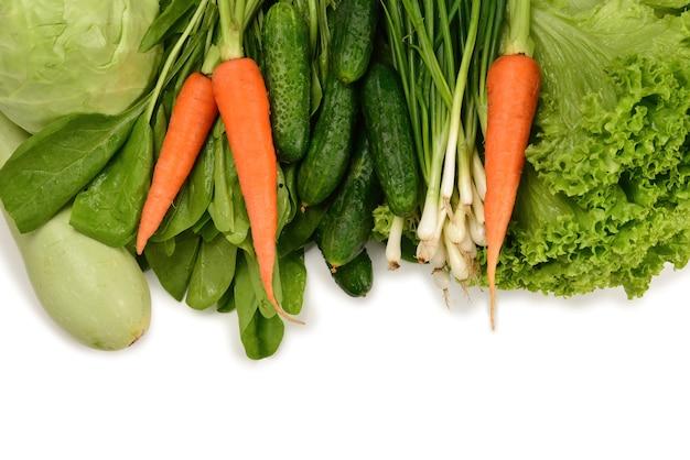 Świeże zielone warzywa i zioła na białym tle