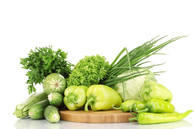 Świeże zielone warzywa na deska do krojenia na białym tle