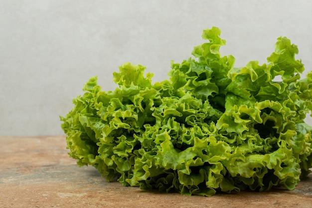 Świeże zielone warzywa na powierzchni marmuru.