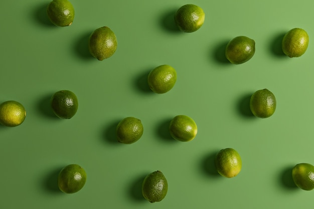 Świeże zielone zdrowe limonki na jasnej powierzchni. owoce cytrusowe używane do akcentowania smaków w potrawach, dekoracji lub dodatków. spożycie produktów roślinnych bogatych w witaminy i minerały dla dobrego zdrowia lub diety