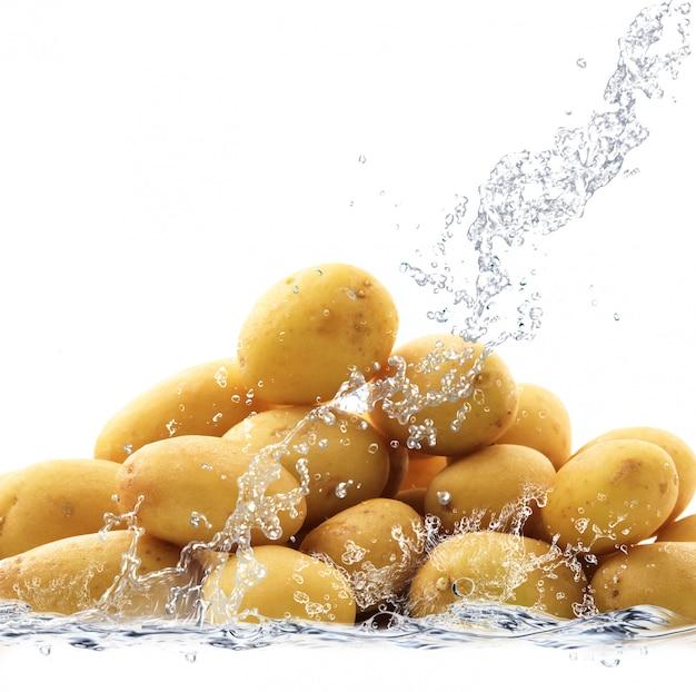 Świeże ziemniaki spadające do wody