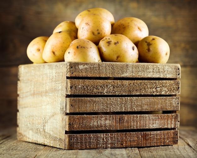 Świeże ziemniaki w drewnianym pudełku