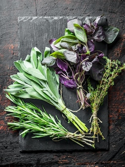 Świeże zioła. szałwia, tymianek, rozmaryn i bazylia na kamiennej desce na rustykalnym stole