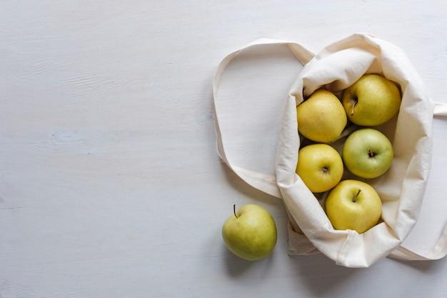 Świeże złote jabłka w sukiennej torbie na zakupy