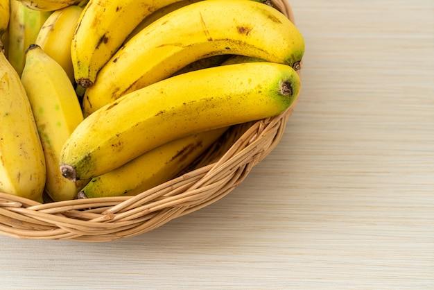 Świeże żółte banany w koszu na stole