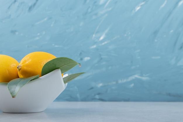 Świeże żółte cytryny na białym talerzu