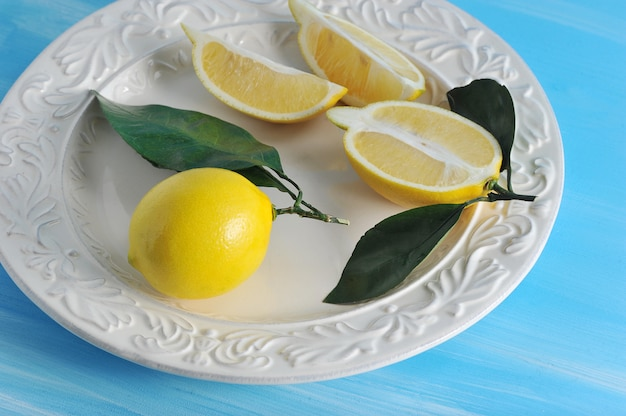 Świeże żółte cytryny z liśćmi na talerzu na błękitnym drewnianym tle