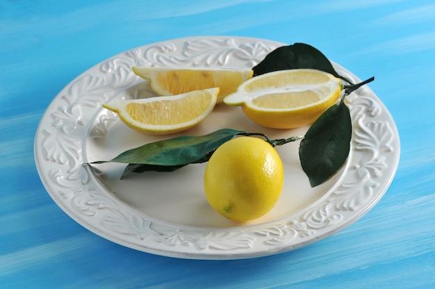 Świeże żółte cytryny z liśćmi na talerzu na błękitnym tle