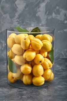 Świeże, żółte morele w szklanym wazonie. owoce na szarym tle. kopia przestrzeń, abstrakcja, fotografia reklamowa.