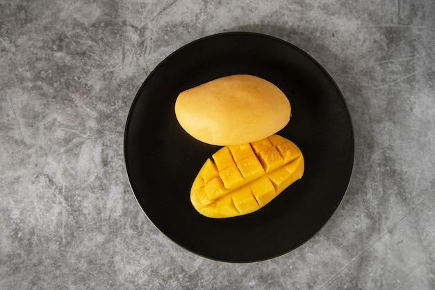 Świeże żółte owoce mango na czarnym talerzu