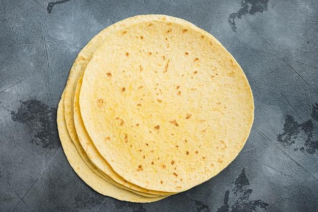 Świeże żółte tortille kukurydziane, na szarym tle, płaski widok z góry z miejsca na kopię