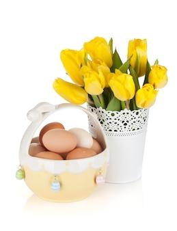 Świeże żółte tulipany i jajka w misce. na białym tle