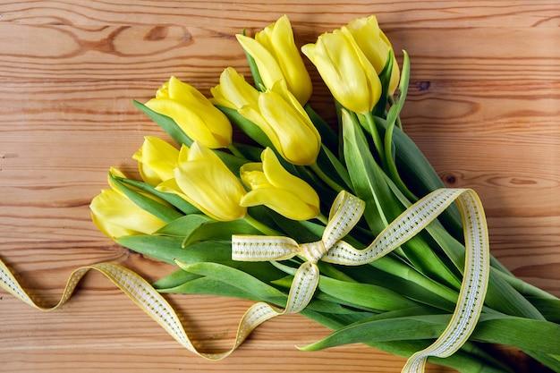 Świeże żółte tulipany z jasną wstążką leżące na stole z drewna