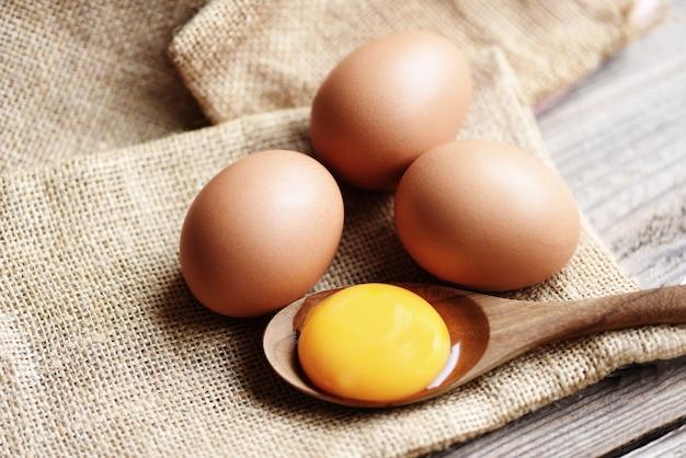 Świeże żółtko na drewnianej łyżce z jajami kurzymi zbiera się z gospodarstwa