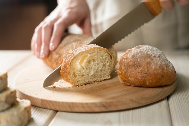 Świeżego chleba plasterek i tnący nóż na wieśniaka stole