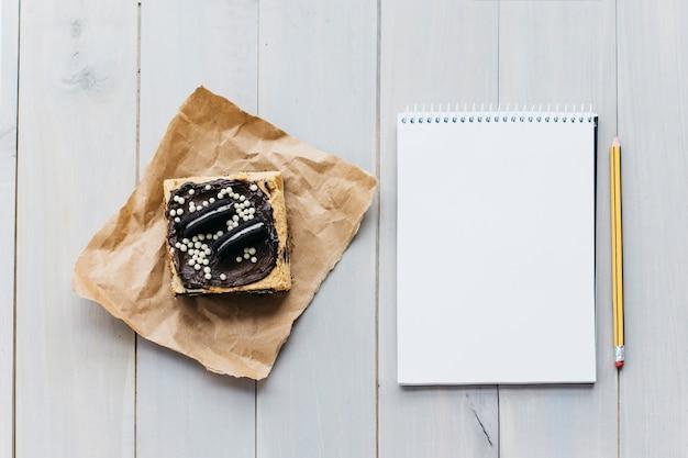 Świeżego ciasta pobliski ślimakowaty notepad i ołówek na drewnianej desce