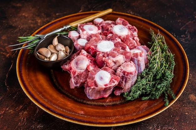 Świeżej niegotowanej wołowiny ogon wołowy pokroić mięso na rustykalnym talerzu z ziołami. ciemne tło. widok z góry.