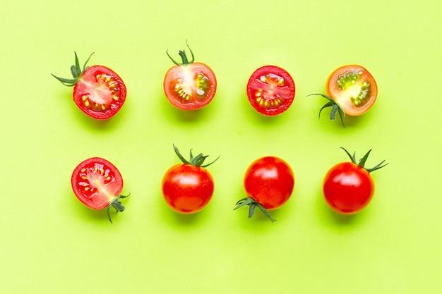 Świezi czereśniowi pomidory, cały i przyrodni cięcie odizolowywający na zielonym tle.