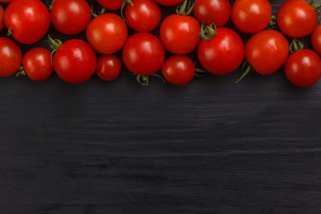 Świezi czereśniowi pomidory na drewnianym czerń stole.