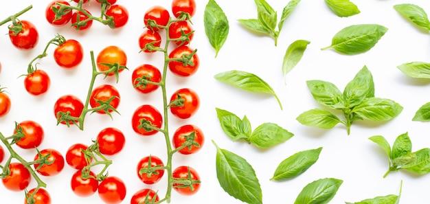Świezi czereśniowi pomidory z basilem opuszczają na białym tle.