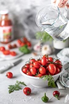 Świezi czerwoni czereśniowi pomidory i basil opuszczają w talerzu na białym kuchennym stole.