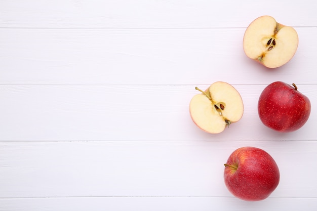 Świezi czerwoni jabłka na biały drewnianym