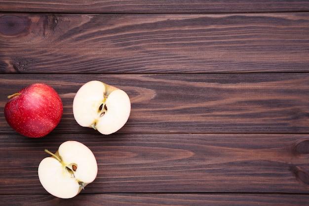 Świezi czerwoni jabłka na brown drewnianym tle