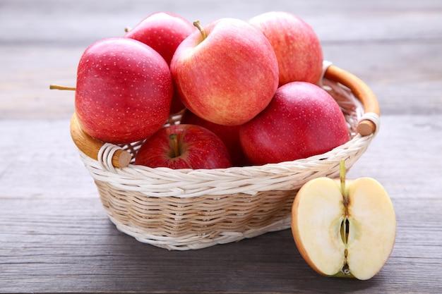 Świezi czerwoni jabłka na drewnianym. świezi czerwoni jabłka w koszu