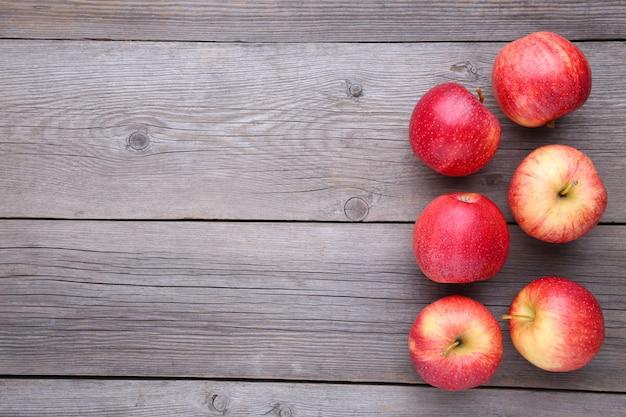 Świezi czerwoni jabłka na szary drewnianym