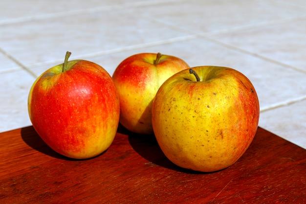 Świezi czerwoni organicznie jabłka na drewnianym stole w letnim dniu