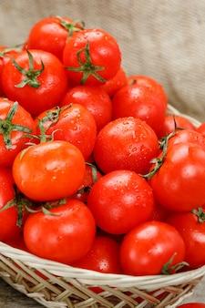 Świezi czerwoni pomidory w łozinowym koszu na starym drewnianym stole. dojrzałe i soczyste pomidory czereśniowe z kroplami wilgoci, szary drewniany stół, wokół płótna juta. w stylu rustykalnym.