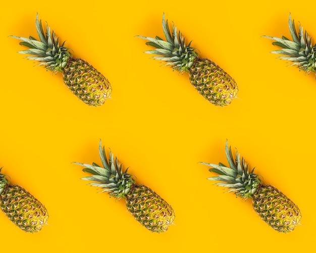 Świezi dojrzali ananasy na żółtym tle. kreatywne mieszkanie leżało z miejsca kopiowania