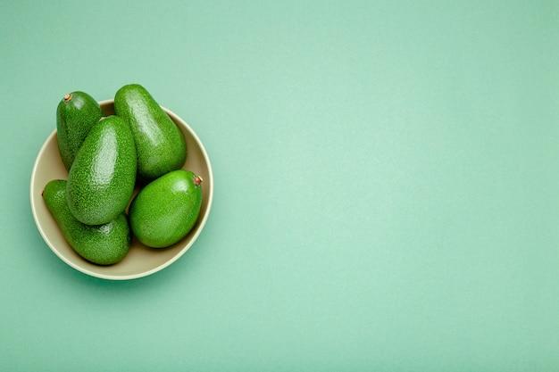 Świezi dojrzali organicznie zieleni avocados w talerzu na koloru tle, odgórnego widoku lata jedzenia pojęcie. minimalne mieszkanie awokado styl płasko świeckich cały owoc na mięty zielonym tle z miejsca kopiowania tekstu.