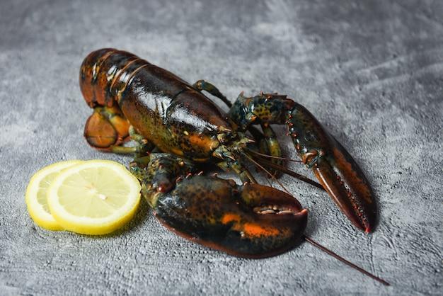 Świezi homarów skorupiaki w owoce morza restauraci dla gotującego jedzenia - surowy homar i cytryna na czarnym kamienia stole, selekcyjna ostrość