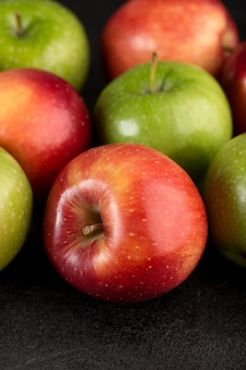 Świezi jabłka czerwień i zielony świeży łagodny dojrzały odosobniony na szarym biurku