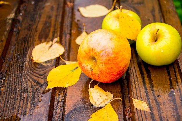 Świezi jabłka na drewnianym stole po deszczu