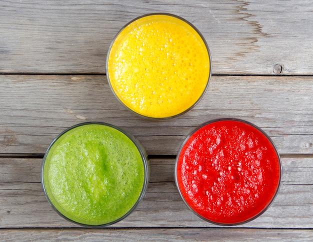 Świezi kolorowi smoothies robić od dzwonkowych pieprzy w szkłach na drewnianym stołowym odgórnym widoku