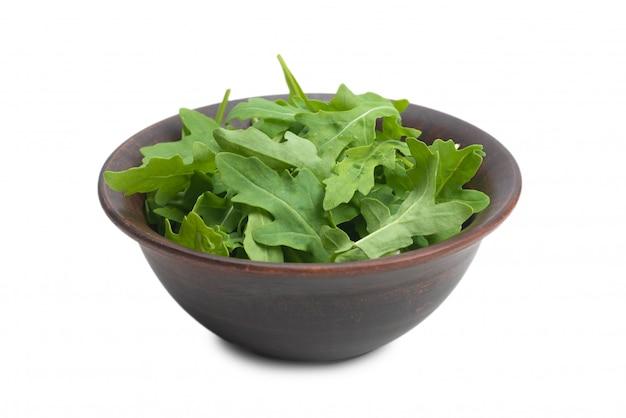 Świezi liście rukola w ceramicznym brown pucharze odizolowywającym.