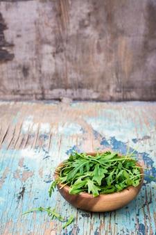 Świezi liście rukola w drewnianym pucharze na drewnianym stole. skopiuj miejsce
