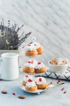 Świezi muffins układali na torta stojaku blisko dokrętki jedzenia nad betonową powierzchnią